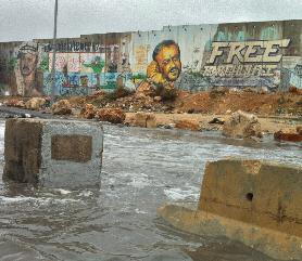"""""""Free Barghouti"""". Straat in Ramallah na regenbui."""