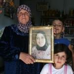 Familieleden met foto van gevangen dochter. (Al Qassem fotogallery)