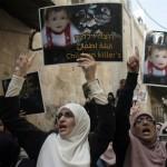 Demonstranten houden foto's van de peuter Dawabsha omhoog.